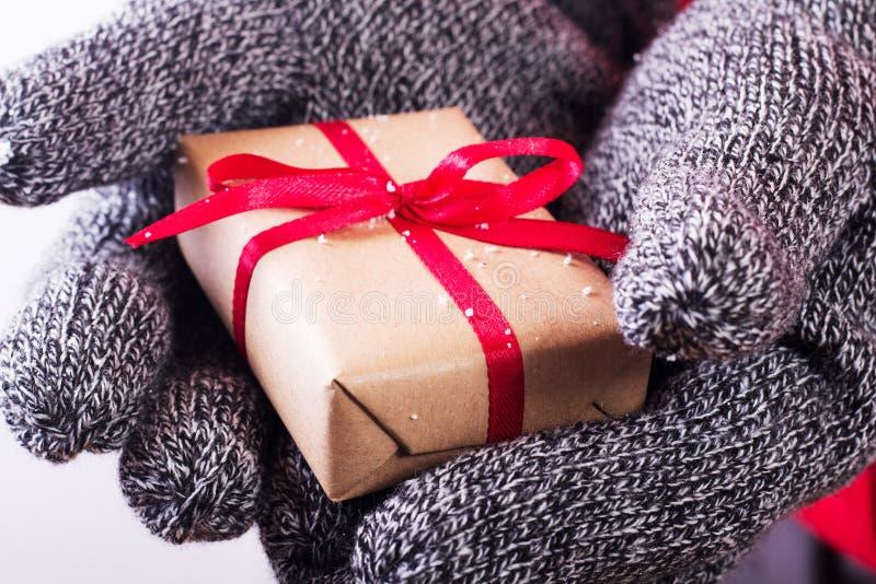 Abra las manos que llevan a cabo un presente envuelto con una cinta roja imagen de archivo
