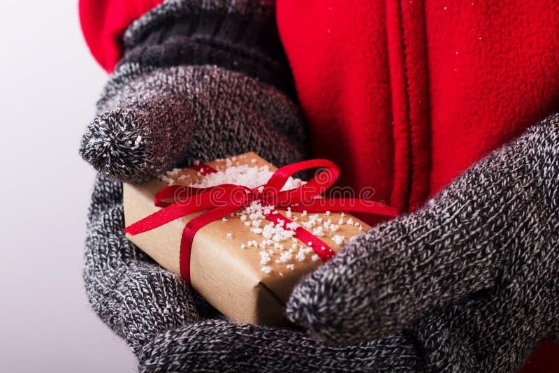 Abra las manos que llevan a cabo un presente envuelto con una cinta roja fotografía de archivo libre de regalías