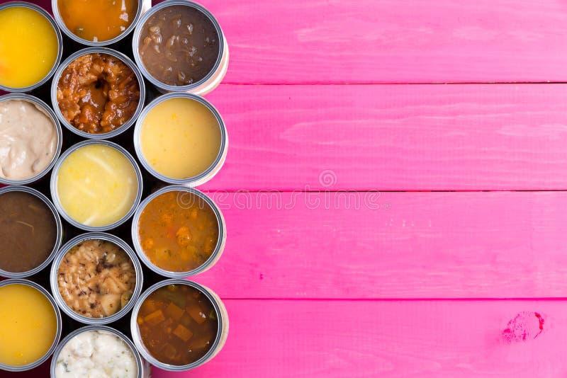 Abra latas da sopa no fundo cor-de-rosa brilhante fotos de stock