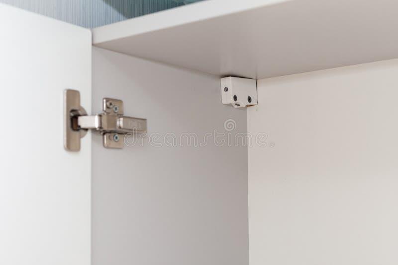 Abra o armário na cozinha Fixando um armário branco novo fotografia de stock