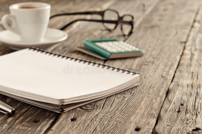 Abra o bloco de notas com pena, xícara de café, calculadora e vidros foto de stock royalty free
