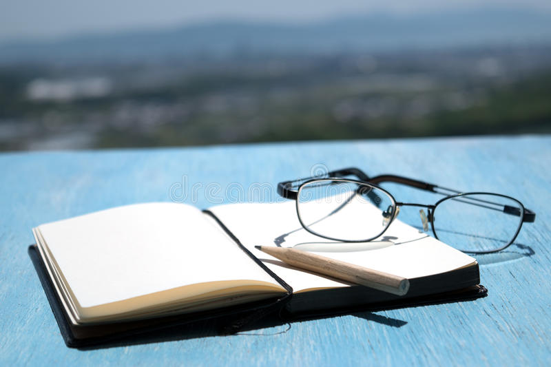 Abra o bloco de notas na tabela azul de madeira foto de stock