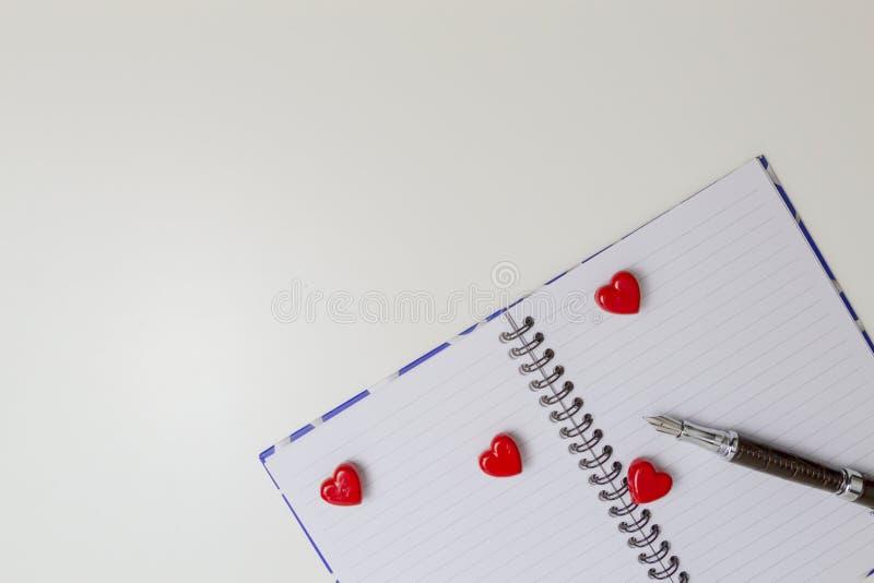 Abra o caderno com corações e a pena vermelhos Vista superior Copie o espaço para o texto foto de stock