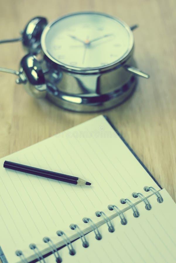 Abra o caderno com lápis e o despertador antiquado na madeira fotografia de stock royalty free