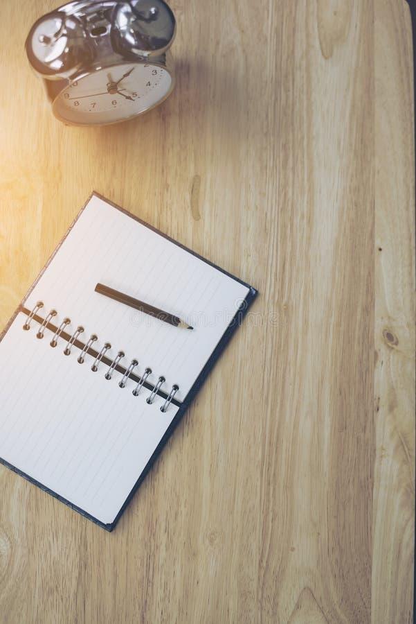 Abra o caderno com lápis e o despertador antiquado na madeira imagens de stock royalty free