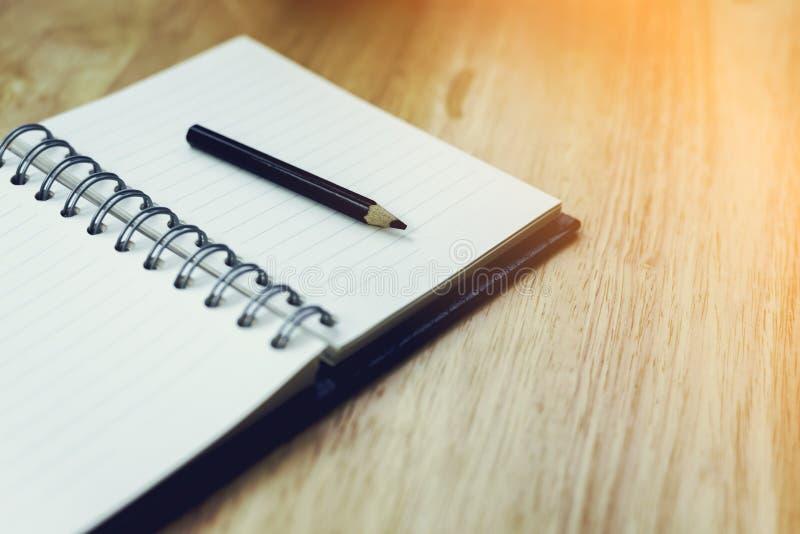 Abra o caderno com lápis e o despertador antiquado na madeira foto de stock royalty free