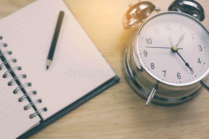 Abra o caderno com lápis e o despertador antiquado na madeira fotos de stock royalty free