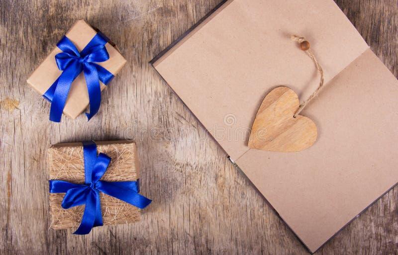 Abra o caderno com páginas vazias, Valentim feito da madeira e caixas com presentes Caixas de presente com fita azul fotografia de stock