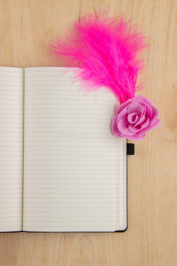 Abra o caderno com white pages e penas cor-de-rosa em uma aba de madeira fotografia de stock royalty free