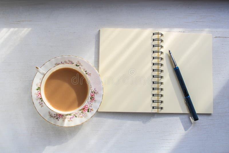 Abra o caderno e o copo do chá em um tampo da mesa ensolarado fotografia de stock royalty free