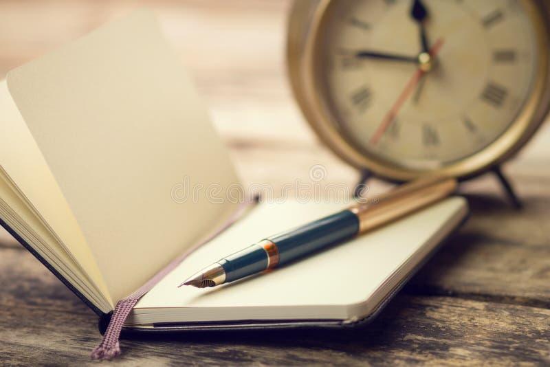 Abra o caderno pequeno com pena de fonte e o despertador antiquado atrás foto de stock
