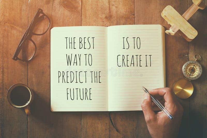 Abra o caderno sobre a tabela de madeira com provérbio inspirador foto de stock