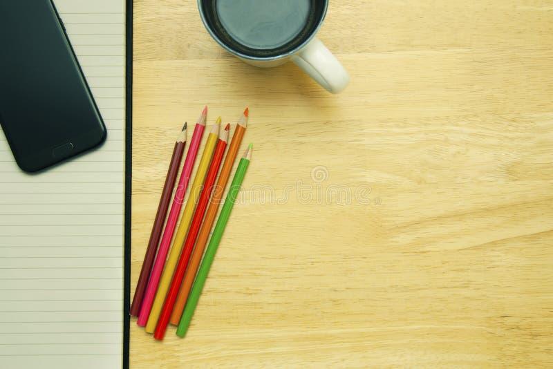 Abra o caderno, a xícara de café e os pastéis na mesa de madeira Copie o espaço fotografia de stock royalty free