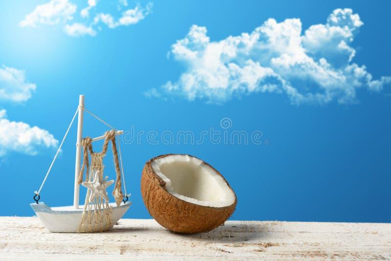 Abra o coco com o modelo de um barco de navigação e do céu azul mim fotos de stock