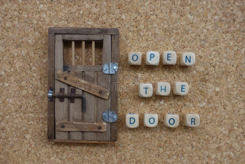 Abra o conceito da porta com uma composição de letras de madeira dos dados e uma miniatura da porta sobre uma placa da cortiça fotos de stock royalty free