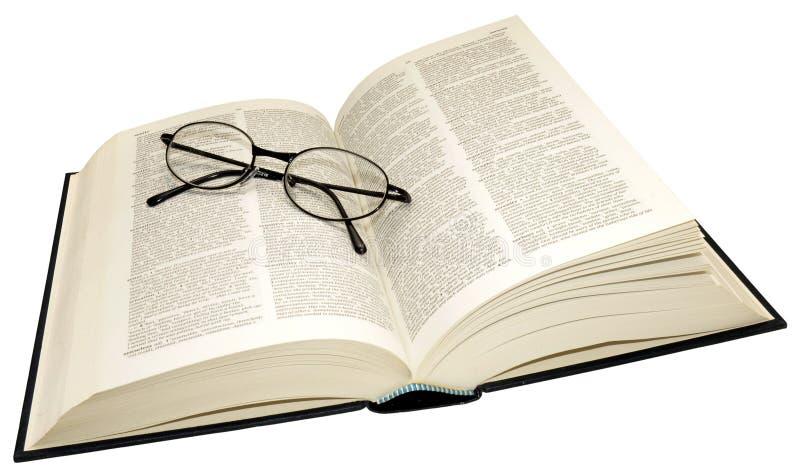Abra o dicionário e os vidros de leitura fotografia de stock