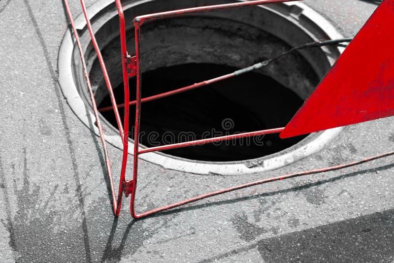 Abra o esgoto com a cerca de advertência vermelha foto de stock