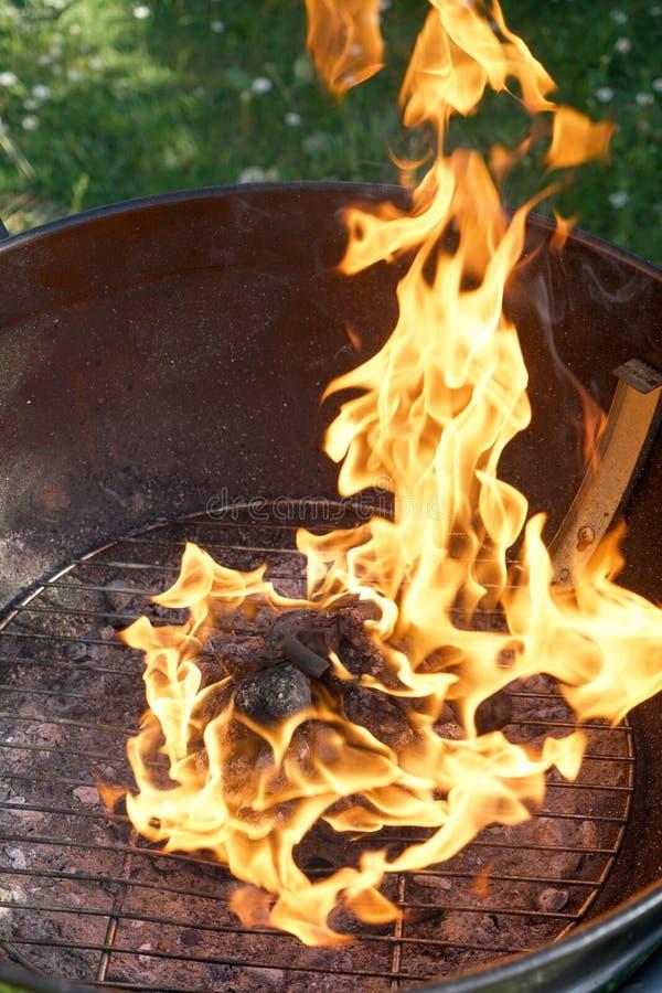 Abra o fogo na grade para grelhar uma salsicha com um assado do carvão vegetal no jardim foto de stock
