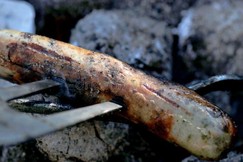 Abra o fogo na grade para grelhar uma salsicha com um assado do carvão vegetal no jardim fotos de stock royalty free