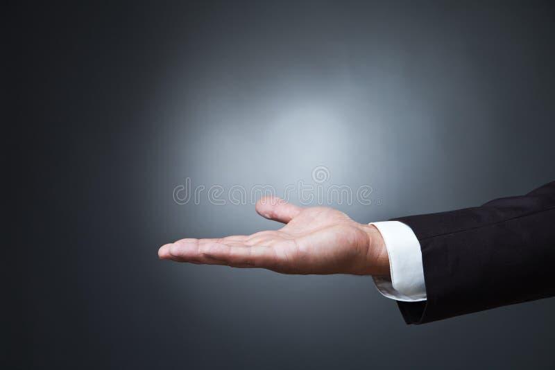 Abra o gesto de mão da palma do homem na obscuridade imagem de stock royalty free