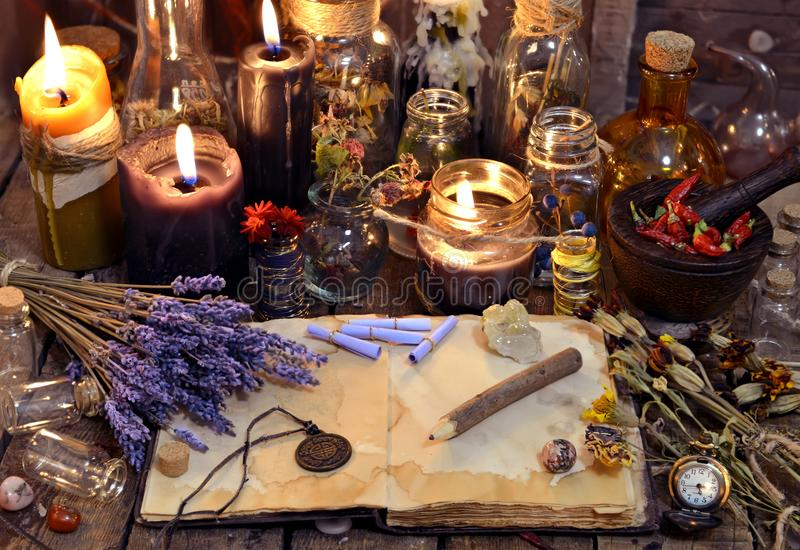 Abra o livro com ervas curas, flores da alfazema, velas, garrafas da poção e objetos mágicos imagens de stock