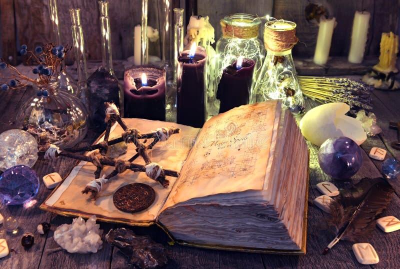 Abra o livro com períodos de magia negra, pentagram, objetos rituais e velas na tabela da bruxa imagem de stock