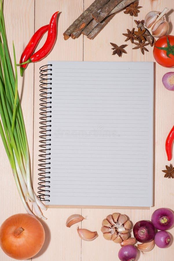 Abra o livro da receita com os legumes frescos na tabela de madeira fotografia de stock royalty free