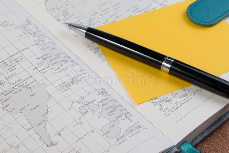 Abra o livro do mapa do diário do negócio com o mapa do mundo com pena fotos de stock