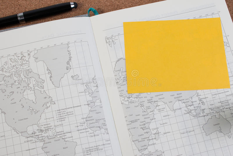 Abra o livro do mapa do diário do negócio com o mapa do mundo com pena imagem de stock