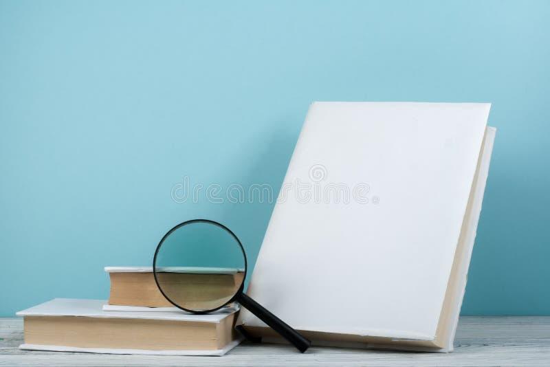 Abra o livro, livros coloridos do livro encadernado na tabela de madeira magnifier De volta à escola Copie o espaço para o texto  imagem de stock