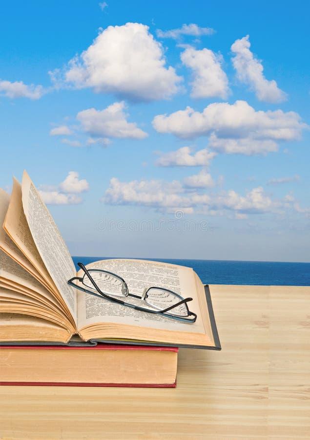 Abra o livro na mesa e no mar imagem de stock royalty free
