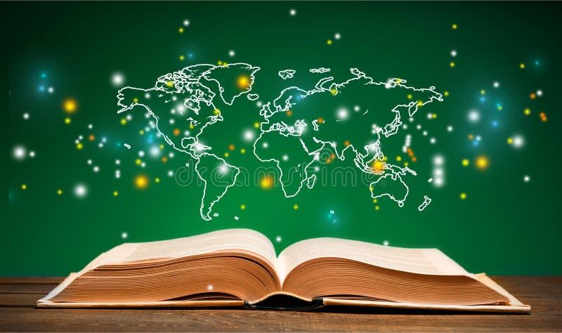 Abra o livro na tabela e no mapa do mundo imagens de stock royalty free
