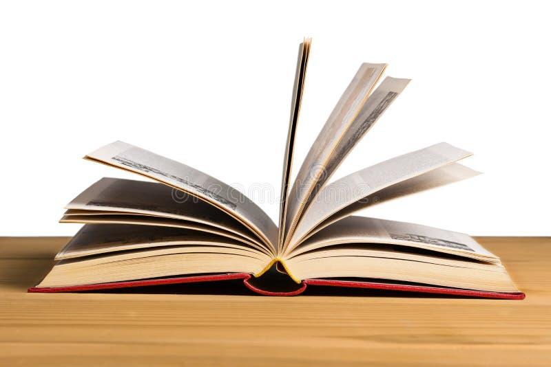 Abra o livro que coloca em uma tabela de madeira isolada foto de stock