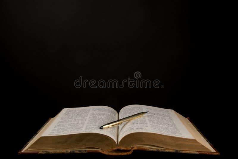 Abra o livro, livro velho com uma pena no meio fotos de stock