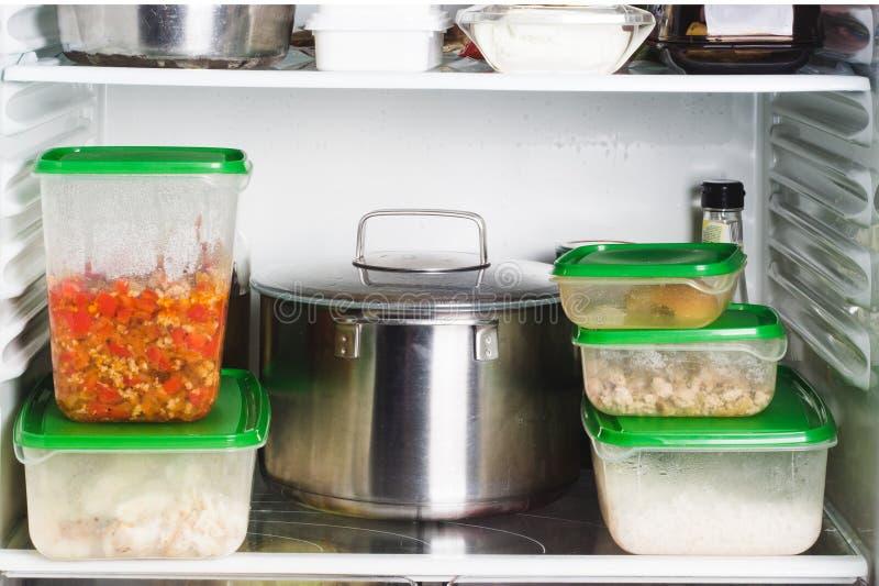 Abra o refrigerador com alimento na cozinha Alimento em uns recipientes, em uma bandeja, e em um frasco nas prateleiras do refrig imagem de stock royalty free
