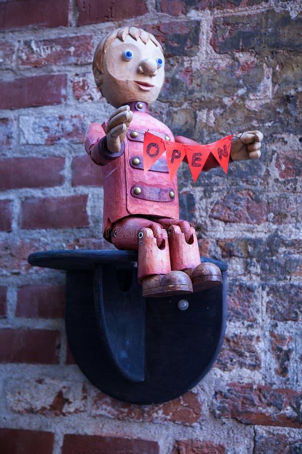 Abra o sinal; Estatueta alemão do menino em uma parede de tijolo foto de stock