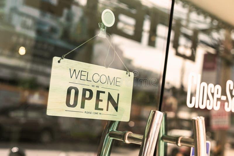 Abra o sinal largo através do vidro da janela na cafetaria imagem de stock