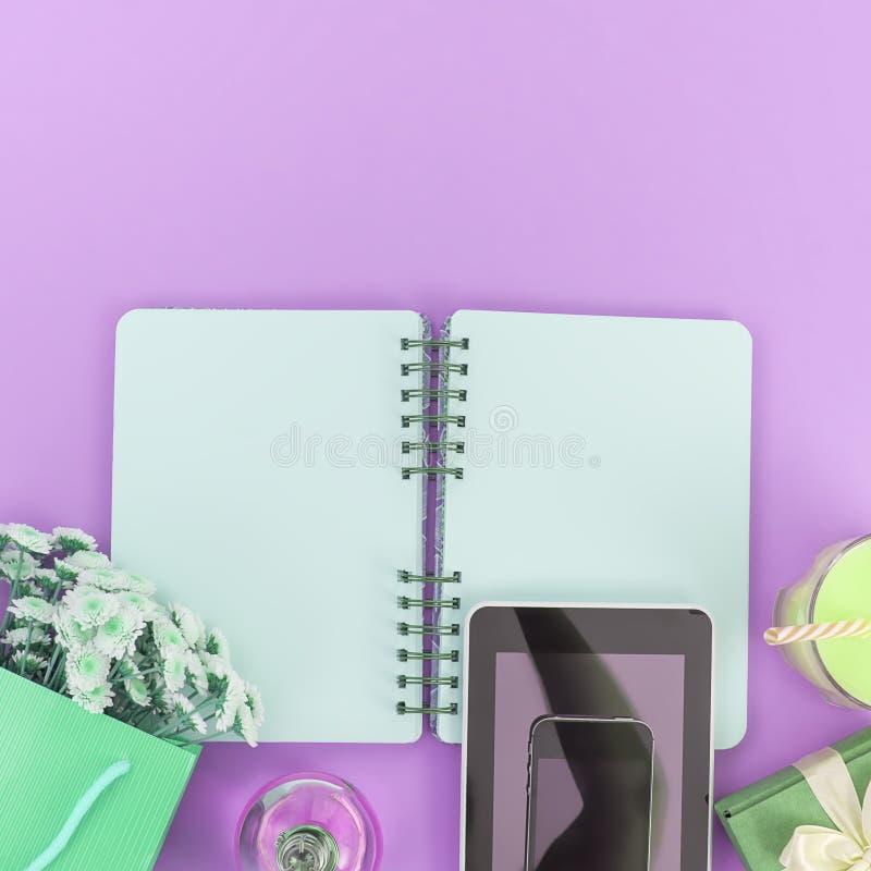 Abra páginas limpas do bloco de notas para escrever um ramalhete das flores em uma tabuleta de vidro do telefone celular do prese imagem de stock