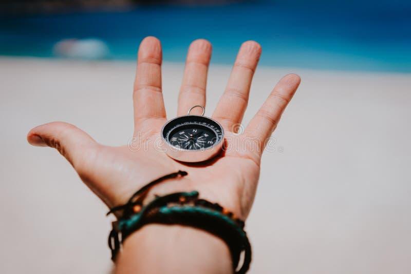 Abra a palma com os dedos esticados que mantêm o compasso preto do metal contra o Sandy Beach branco Encontre seu conceito da man fotos de stock