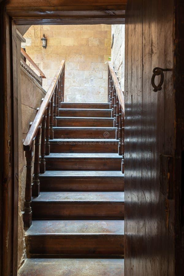 Abra a porta de madeira que revela a escadaria velha de madeira que vai acima com com reflexões das escadas na porta imagem de stock royalty free