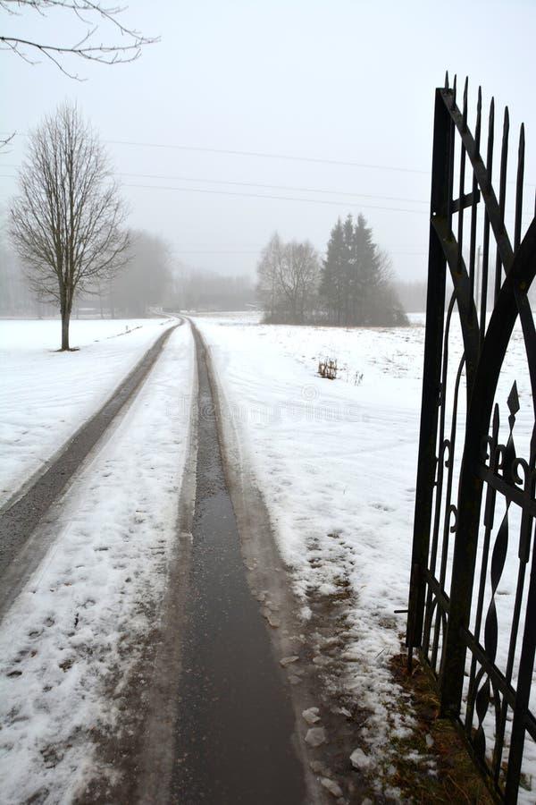 Abra a porta do metal e a estrada do parque no inverno fotos de stock royalty free