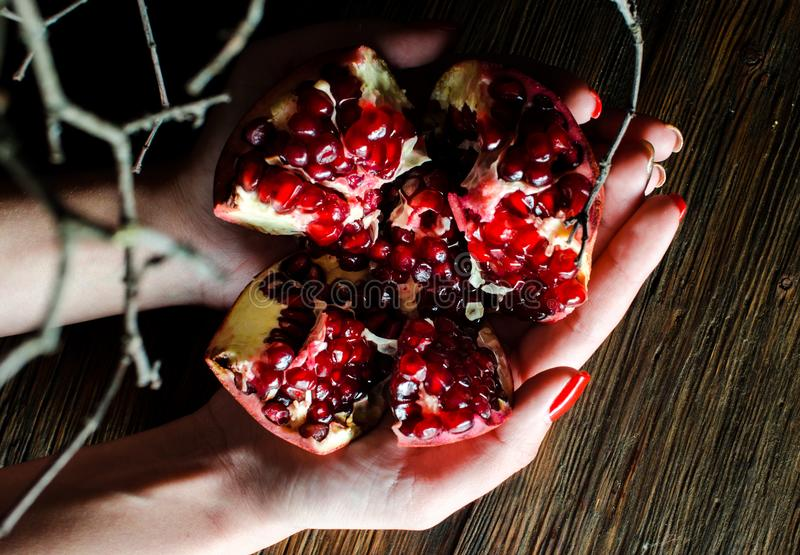 Abra romã maduras frescas nas mãos fêmeas em um fundo de madeira fotografia de stock royalty free