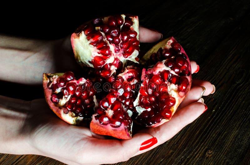 Abra romã maduras frescas nas mãos fêmeas em um fundo de madeira fotos de stock
