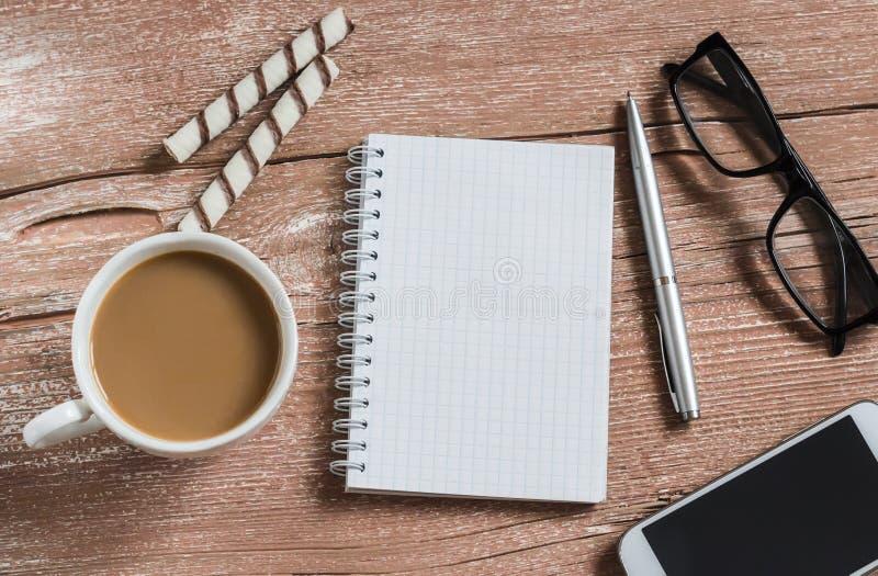 Abra um bloco de notas, uma pena, uns vidros, um telefone, uma xícara de café e uns biscoitos limpos A ruptura de café do escritó imagem de stock