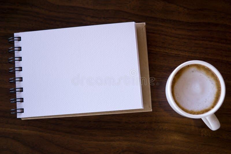 Abra um caderno branco vazio com café quente na tabela imagens de stock royalty free