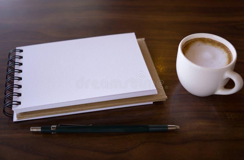 Abra um caderno branco vazio com café quente na tabela fotos de stock royalty free