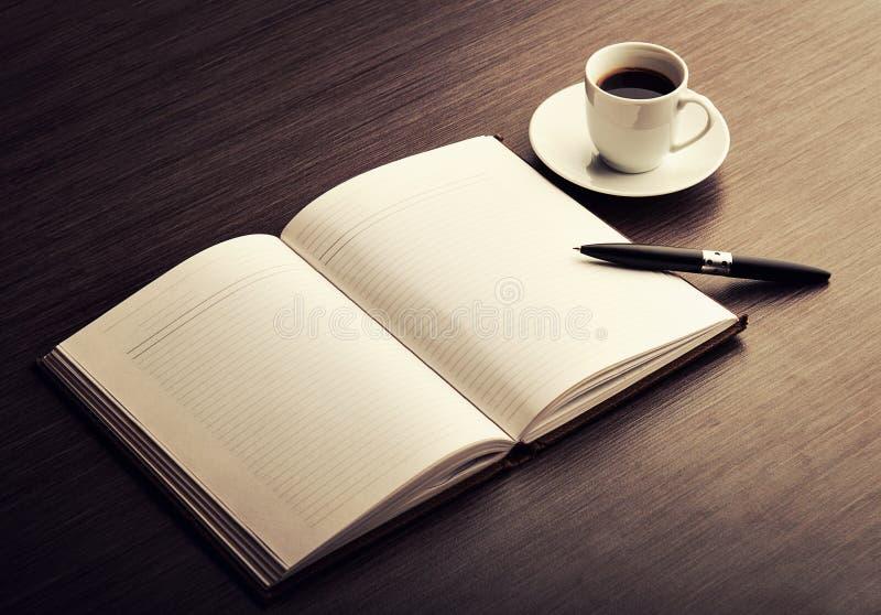 Abra un cuaderno, una pluma y un café blancos en blanco en el escritorio imagen de archivo