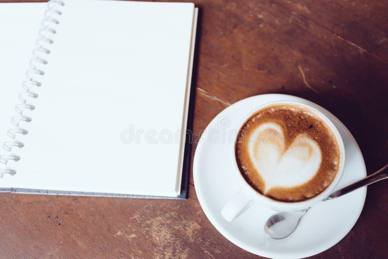 Abra un cuaderno y una taza de café blancos en blanco fotografía de archivo libre de regalías