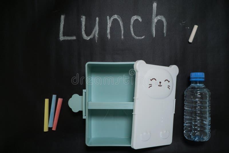 Abra una fiambrera vacía con una pequeña cara dulce y una botella de agua en un fondo negro con los creyones y el almuerzo colori foto de archivo libre de regalías