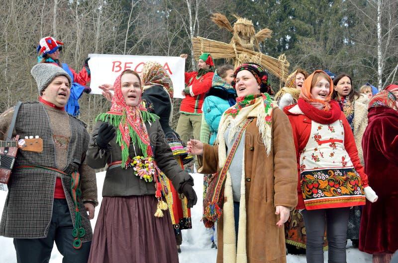 Abramtsevo,莫斯科地区,俄罗斯, 3月, 13日 2016年 参与为庆祝Bakshevskaya Shrovetide的人们在秸杆肖象附近 免版税图库摄影